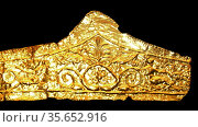 Gold pediment-shaped diadems 330-300BC. These diadems are made of thin sheet gold with die-formed designs.  The most elaborate of them has a central palmette and winged figures on either side with scroll work beyond.  The Kyme Treasure contained fragments of at least 11 such diadems; they were probably especially made for the tomb. Редакционное фото, агентство World History Archive / Фотобанк Лори