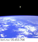 An astronaut shown floating in space above the earth. Редакционное фото, агентство World History Archive / Фотобанк Лори