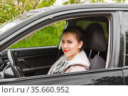 A young woman is sitting in a car smiling and looking at the camera through the window opening. Стоковое фото, фотограф Владимир Ушаров / Фотобанк Лори