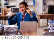 Young male employee holding moneybag in remuneration concept. Стоковое фото, фотограф Elnur / Фотобанк Лори