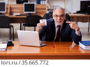 Old male employee playing cards at workplace. Стоковое фото, фотограф Elnur / Фотобанк Лори