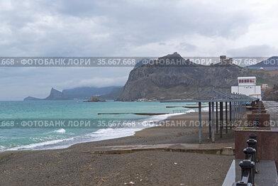 Не сезон. Пустой пляж в Судакской бухте, вид в сторону Генуэзской крепости. Крым, весна, начало апреля, пасмурно, плохая погода.