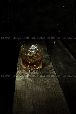 Isolated shot of whiskey with splash on black background and wooden table