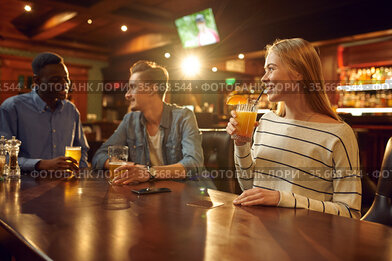 Friends with alcohol beverages having fun in bar