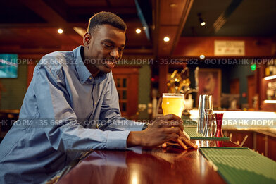 Young man drinks fresh beer at the counter in bar