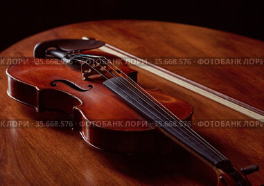 Violin in retro style and bow on wooden table