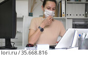 Woman in protective mask sitting at workplace with computer in her office. Стоковое видео, видеограф Яков Филимонов / Фотобанк Лори