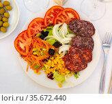 Catalan salad with lettuce, tomatoes and olives with sausages and cured meat. Стоковое фото, фотограф Яков Филимонов / Фотобанк Лори