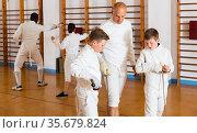 Coach demonstrating fencing movements to kids. Стоковое фото, фотограф Яков Филимонов / Фотобанк Лори