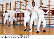 Focused boys fencers attentively listening to professional fencing coach in gym. Стоковое фото, фотограф Яков Филимонов / Фотобанк Лори