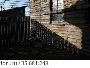 Тень от забора на фасаде деревянного сарая. Редакционное фото, фотограф Дмитрий Неумоин / Фотобанк Лори