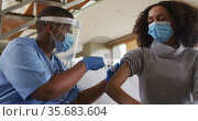 African american female doctor wearing face mask vaccinating african american patient. Стоковое видео, агентство Wavebreak Media / Фотобанк Лори