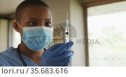 African american female doctor wearing face mask preparing covid vaccine for patient. Стоковое видео, агентство Wavebreak Media / Фотобанк Лори