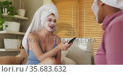 Diverse happy female friends wearing towels on heads and cleansing masks using smartphone at home. Стоковое видео, агентство Wavebreak Media / Фотобанк Лори
