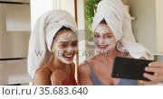 Diverse happy female friends wearing towels on heads and cleansing masks taking selfie at home. Стоковое видео, агентство Wavebreak Media / Фотобанк Лори