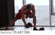 Athletic muscular shirtless man training his hands muscles with a dumbbell. Стоковое видео, видеограф Константин Шишкин / Фотобанк Лори