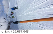 Подъем на гору на бугельном подъемнике на горнолыжном курорте, вертикальное видео. Стоковое видео, видеограф Кекяляйнен Андрей / Фотобанк Лори