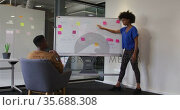 African american businesswoman standing at whiteboard giving presentation to colleague. Стоковое видео, агентство Wavebreak Media / Фотобанк Лори