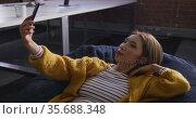 Asian business woman lying on bean bag taking selfie and smiling during break. Стоковое видео, агентство Wavebreak Media / Фотобанк Лори