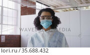 Portrait of mixed race female cleaner wearing protective face mask and overalls. Стоковое видео, агентство Wavebreak Media / Фотобанк Лори