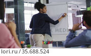Mixed race woman standing at whiteboard giving presentation to diverse group of colleagues. Стоковое видео, агентство Wavebreak Media / Фотобанк Лори
