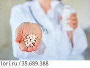 Ärztin hält Tabletten in ihrer Hand als Konzept für Pharmazie und... Стоковое фото, фотограф Zoonar.com/Robert Kneschke / age Fotostock / Фотобанк Лори