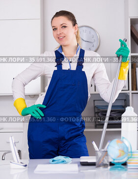 Smiling girl cleaning the room