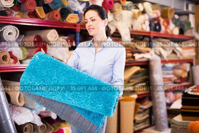 Smiling woman customer choosing colored carpet