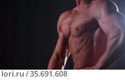 Sports training - athletic muscular shirtless man showing his muscles in the dark. Стоковое видео, видеограф Константин Шишкин / Фотобанк Лори