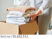 Frau packt Kleidung in Umzugskarton für Umzug oder Kleiderspende. Стоковое фото, фотограф Zoonar.com/Robert Kneschke / age Fotostock / Фотобанк Лори