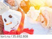 Lachende Familie beim Schneemann bauen im Winter im Schnee. Стоковое фото, фотограф Zoonar.com/Robert Kneschke / age Fotostock / Фотобанк Лори