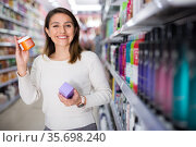 Young Latina choosing haircare cosmetics in specialized boutique. Стоковое фото, фотограф Татьяна Яцевич / Фотобанк Лори