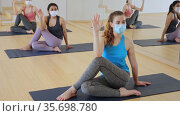 Group of attractive women in fase masks practice yoga pose to meditation in modern studio. Стоковое видео, видеограф Яков Филимонов / Фотобанк Лори