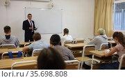 Male speaker giving lesson for teenage students in classroom. Стоковое видео, видеограф Яков Филимонов / Фотобанк Лори