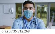 Portrait of mixed race male doctor wearing scrubs and face mask standing in hospital. Стоковое видео, агентство Wavebreak Media / Фотобанк Лори