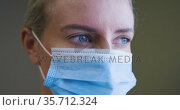 Portrait of caucasian female doctor wearing face mask looking to camera. Стоковое видео, агентство Wavebreak Media / Фотобанк Лори
