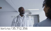African american male and female senior doctors talking to each other at hospital. Стоковое видео, агентство Wavebreak Media / Фотобанк Лори