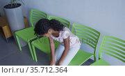 African american girl sitting on a chair in the corridor at hospital. Стоковое видео, агентство Wavebreak Media / Фотобанк Лори