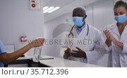 Diverse hospital worker disinfecting hands of doctors all wearing face masks. Стоковое видео, агентство Wavebreak Media / Фотобанк Лори