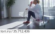 Tired caucasian female doctor sitting on stairs in hospital corridor. Стоковое видео, агентство Wavebreak Media / Фотобанк Лори