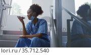 Mixed race female doctor wearing face mask sitting on stairs in hospital talking on smartphone. Стоковое видео, агентство Wavebreak Media / Фотобанк Лори