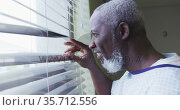 African american male patient looking at window in hospital room smiling. Стоковое видео, агентство Wavebreak Media / Фотобанк Лори