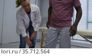 Diverse female orthopedic doctor examining male patient in doctors office. Стоковое видео, агентство Wavebreak Media / Фотобанк Лори