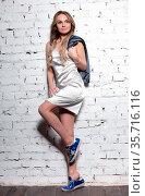 Sexy blonde posing in studio dressed in sportswear, short dress and... Стоковое фото, фотограф Zoonar.com/Sergey Sukhorukov / easy Fotostock / Фотобанк Лори
