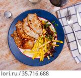Tasty hearty lunch of roasted steaks of pork loin served with fried potatoes. Стоковое фото, фотограф Яков Филимонов / Фотобанк Лори