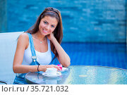 Young woman having a breakfast with coffee and cake sitting outdoors... Стоковое фото, фотограф Zoonar.com/Ivan Mikhaylov / easy Fotostock / Фотобанк Лори