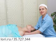 Professional female beautician doing facial massage to woman in spa salon. Стоковое фото, фотограф Евгений Харитонов / Фотобанк Лори