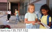 Portrait of two primary school girls talking outside before lesson. Стоковое видео, видеограф Яков Филимонов / Фотобанк Лори