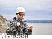 Woman geologist examines a mineral sample at the edge of the quarry. Стоковое фото, фотограф Евгений Харитонов / Фотобанк Лори