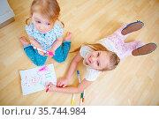 Zwei Kinder von oben beim Malen von einem Bild mit Filzstiften. Стоковое фото, фотограф Zoonar.com/Robert Kneschke / age Fotostock / Фотобанк Лори